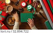Купить «hands packing christmas gift and choosing bow», видеоролик № 32894722, снято 18 декабря 2019 г. (c) Syda Productions / Фотобанк Лори