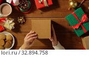 Купить «woman closing empty christmas gift on wooden table», видеоролик № 32894758, снято 18 декабря 2019 г. (c) Syda Productions / Фотобанк Лори