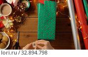 Купить «woman wrapping christmas gift and tying bow», видеоролик № 32894798, снято 18 декабря 2019 г. (c) Syda Productions / Фотобанк Лори
