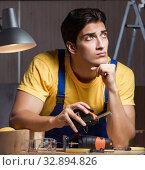 Купить «The worker working in repair workshop in woodworking concept», фото № 32894826, снято 11 августа 2017 г. (c) Elnur / Фотобанк Лори
