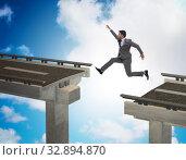 Купить «Young businessman jumping over the bridge», фото № 32894870, снято 28 января 2020 г. (c) Elnur / Фотобанк Лори