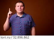 Купить «Studio shot of overweight young man wearing purple checkered shirt against brown background», фото № 32896862, снято 23 февраля 2020 г. (c) easy Fotostock / Фотобанк Лори