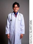 Купить «Studio shot of young handsome Asian man doctor wearing eyeglasses against gray background», фото № 32897006, снято 27 мая 2020 г. (c) easy Fotostock / Фотобанк Лори