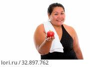Купить «Studio shot of young happy fat Asian woman smiling while giving red apple», фото № 32897762, снято 23 февраля 2020 г. (c) easy Fotostock / Фотобанк Лори