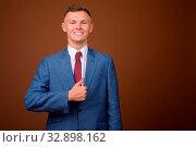 Купить «Studio shot of young businessman wearing suit against brown background», фото № 32898162, снято 23 февраля 2020 г. (c) easy Fotostock / Фотобанк Лори