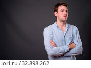 Купить «Studio shot of young handsome man wearing blue shirt against gray background», фото № 32898262, снято 23 февраля 2020 г. (c) easy Fotostock / Фотобанк Лори