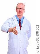 Купить «Studio shot of happy man doctor smiling and standing while giving handshake», фото № 32898362, снято 23 февраля 2020 г. (c) easy Fotostock / Фотобанк Лори