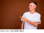 Купить «Studio shot of young man wearing white shirt against brown background», фото № 32898462, снято 23 февраля 2020 г. (c) easy Fotostock / Фотобанк Лори