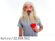 Купить «Studio shot of happy senior bearded man smiling and holding red heart ready for Valentine's day», фото № 32898562, снято 23 февраля 2020 г. (c) easy Fotostock / Фотобанк Лори
