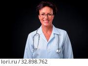 Купить «Studio shot of mature beautiful Scandinavian woman doctor with short hair against black background», фото № 32898762, снято 23 февраля 2020 г. (c) easy Fotostock / Фотобанк Лори