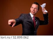 Купить «Studio shot of businessman wearing suit against brown background», фото № 32899062, снято 23 февраля 2020 г. (c) easy Fotostock / Фотобанк Лори