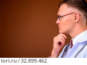 Купить «Studio shot of young man doctor wearing eyeglasses against brown background», фото № 32899462, снято 23 февраля 2020 г. (c) easy Fotostock / Фотобанк Лори