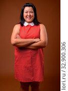 Купить «Studio shot of beautiful overweight Asian woman wearing red dress against brown background», фото № 32900306, снято 27 мая 2020 г. (c) easy Fotostock / Фотобанк Лори
