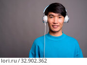 Studio shot of young Asian man listening to music against gray background. Стоковое фото, фотограф Zoonar.com/Toni Rantala / easy Fotostock / Фотобанк Лори