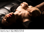 Stripper in unbuttoned jacket on sofa shot. Стоковое фото, фотограф Гурьянов Андрей / Фотобанк Лори