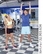 Купить «Couple during weightlifting workout», фото № 32903634, снято 16 июля 2018 г. (c) Яков Филимонов / Фотобанк Лори