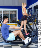 Купить «Young fitness man and woman doing cardio workout on fitness machines at gym», фото № 32903730, снято 16 июля 2018 г. (c) Яков Филимонов / Фотобанк Лори