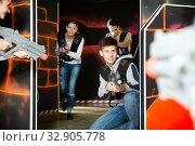 Купить «Group of young people playing laser tag game with laser guns», фото № 32905778, снято 27 мая 2020 г. (c) Яков Филимонов / Фотобанк Лори