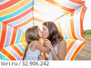Купить «Mom with a small daughter walks along the beach with an umbrella on a sunny summer day.», фото № 32906242, снято 18 июля 2019 г. (c) Акиньшин Владимир / Фотобанк Лори