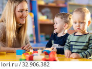 Купить «Teacher and cute little girl play with blocks toy in preschool», фото № 32906382, снято 26 мая 2020 г. (c) Оксана Кузьмина / Фотобанк Лори