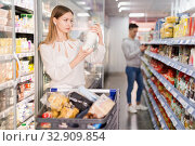 Portrait of young woman with shopping cart choosing dairy products in supermarket. Стоковое фото, фотограф Яков Филимонов / Фотобанк Лори