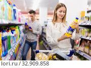 Купить «Portrait of young woman with shopping cart choosing household chemicals in supermarket», фото № 32909858, снято 7 ноября 2019 г. (c) Яков Филимонов / Фотобанк Лори