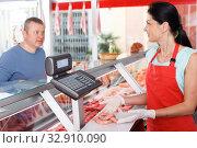 Купить «Female seller weighing sausages for customer», фото № 32910090, снято 22 июня 2018 г. (c) Яков Филимонов / Фотобанк Лори