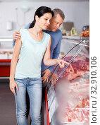 Купить «Positive couple choosing meat and discussing», фото № 32910106, снято 22 июня 2018 г. (c) Яков Филимонов / Фотобанк Лори