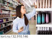 Portrait of young Asian woman choosing hair balm in supermarket. Стоковое фото, фотограф Яков Филимонов / Фотобанк Лори