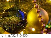 Купить «Елочные шары и бусы на елке. Крупный план», фото № 32910430, снято 5 января 2020 г. (c) Наталья Николаева / Фотобанк Лори