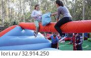 Купить «Female friends having funny wrestling by pillows on inflatable beam in outdoor amusement park», видеоролик № 32914250, снято 12 ноября 2019 г. (c) Яков Филимонов / Фотобанк Лори