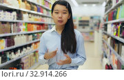Купить «Portrait of cheerful young Asian woman behind counter demonstrating hair dye products», видеоролик № 32914266, снято 20 февраля 2020 г. (c) Яков Филимонов / Фотобанк Лори