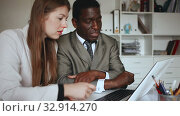 Купить «Young woman and man colleagues working at laptop and discussing in office», видеоролик № 32914270, снято 26 апреля 2019 г. (c) Яков Филимонов / Фотобанк Лори