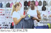 Купить «Portrait of happy man and woman holding sportswear in sporting goods store», видеоролик № 32914278, снято 21 февраля 2020 г. (c) Яков Филимонов / Фотобанк Лори