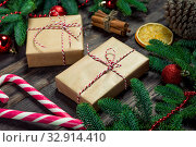 Купить «Two retro-style gifts with a red twine and candy cane surrounded by spruce branches close-up on dark boards», фото № 32914410, снято 30 декабря 2018 г. (c) Константин Лабунский / Фотобанк Лори