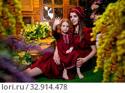 Easter. Family in rural wooden interior with flower in studio. Mother and daughter in maroon or red dresses of the village shepherdesses. Стоковое фото, фотограф Кривошеина Елена Леонидовна / Фотобанк Лори