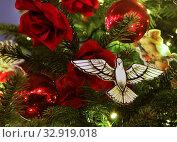 Купить «Украшения новогодней елки: белый голубь, красные шары, цветы  и лампочки», фото № 32919018, снято 5 января 2020 г. (c) Наталья Николаева / Фотобанк Лори