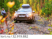 Russia, Bashkortostan, September 2019: Mitsubishi ASX crossover car overcomes a steep climb along a gravel road through a dense forest with headlights on. Редакционное фото, фотограф Акиньшин Владимир / Фотобанк Лори
