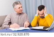 Adult father and son discuss contract. Стоковое фото, фотограф Яков Филимонов / Фотобанк Лори