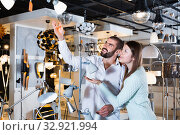 Smiling couple customers choosing floor lamp with a long standard in store. Стоковое фото, фотограф Яков Филимонов / Фотобанк Лори