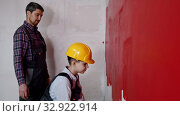 A little boy in helmet painting walls with red paint - his father watching him. Стоковое видео, видеограф Константин Шишкин / Фотобанк Лори