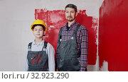A little boy and his father painting walls - a boy puts on a helmet. Стоковое видео, видеограф Константин Шишкин / Фотобанк Лори