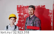 Smiling little boy and his father painting walls - pulls out their rollers and the boy puts on helmet. Стоковое видео, видеограф Константин Шишкин / Фотобанк Лори