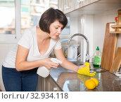 Купить «Woman with rag cleaning kitchen», фото № 32934118, снято 22 ноября 2018 г. (c) Яков Филимонов / Фотобанк Лори