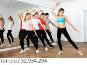 Group of teenage boys and girls exercising with female coach in choreography class. Стоковое фото, фотограф Яков Филимонов / Фотобанк Лори