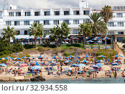 Crowd of sunbathing people is on Coral Bay beach. All Cyprus beaches full of vacationers and Mediterranean sea with swimmers in water the year round. Cyprus (2013 год). Редакционное фото, фотограф Кекяляйнен Андрей / Фотобанк Лори