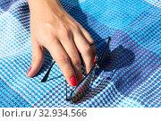 Female hand with red nails lying on blue fabric with sunglasses, people sunbathing. Стоковое фото, фотограф Кекяляйнен Андрей / Фотобанк Лори