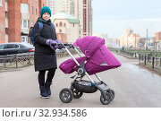 Young mother pushing stroller at street. Cold weather, woman dressed in warm clothing with windbreaker mittens. Стоковое фото, фотограф Кекяляйнен Андрей / Фотобанк Лори