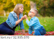 Mom and boy teen sit on green glade and blow off dandelion. Стоковое фото, фотограф Иванов Алексей / Фотобанк Лори