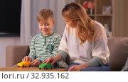 Купить «mother and son playing with toy cars at home», видеоролик № 32935162, снято 23 декабря 2019 г. (c) Syda Productions / Фотобанк Лори